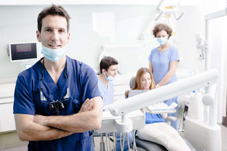 Junger Zahnarzt mit Team